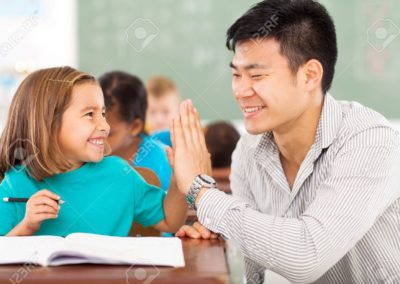 21191547-cheerful-elementary-school-teacher-and-student-high-five-in-classroom